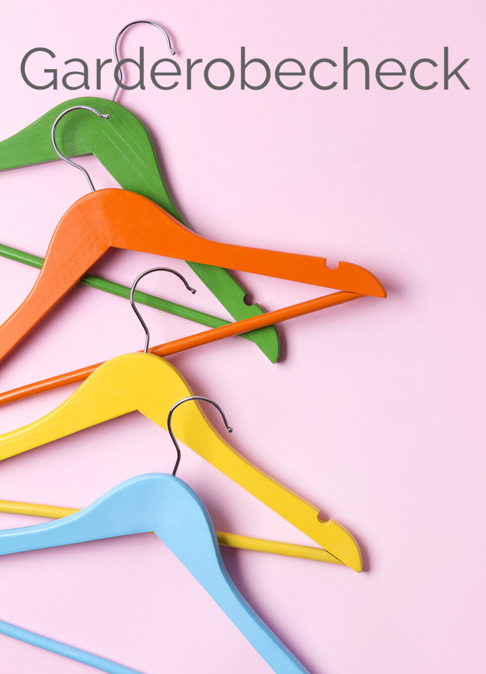 Creative flat lay multicolor wooden hangers at pink pastel background with copy space minimalist style.